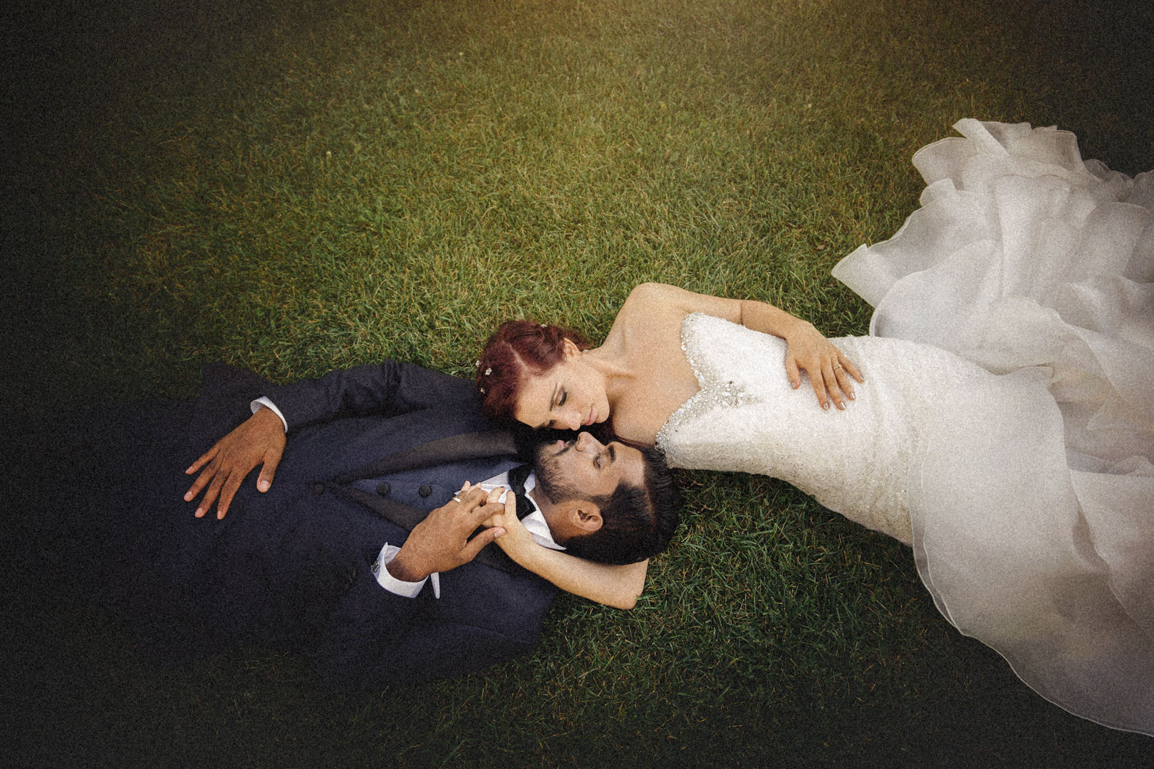 Romantic pose of a couple laying together on grass