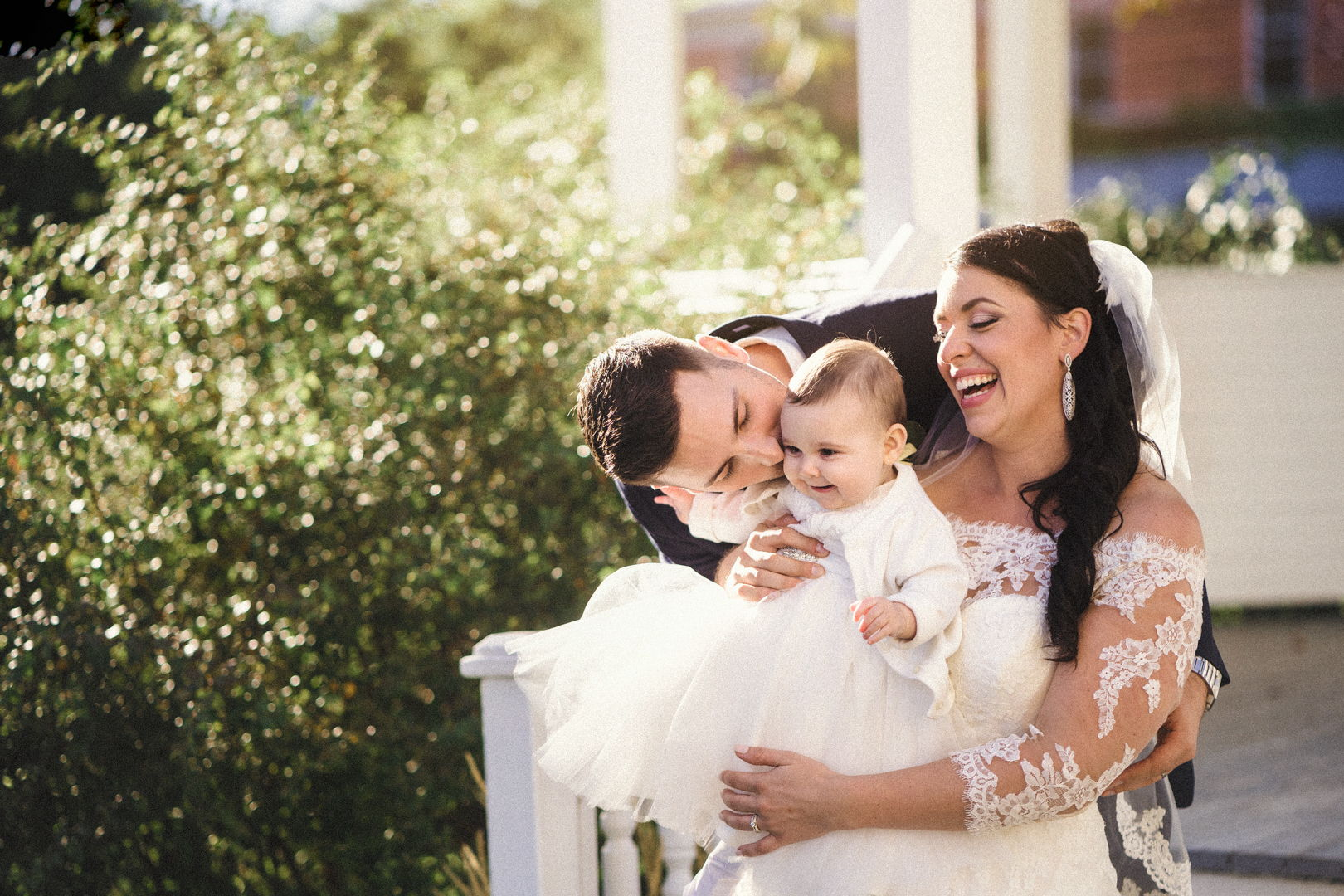 Happy couple with their baby girl at their wedding