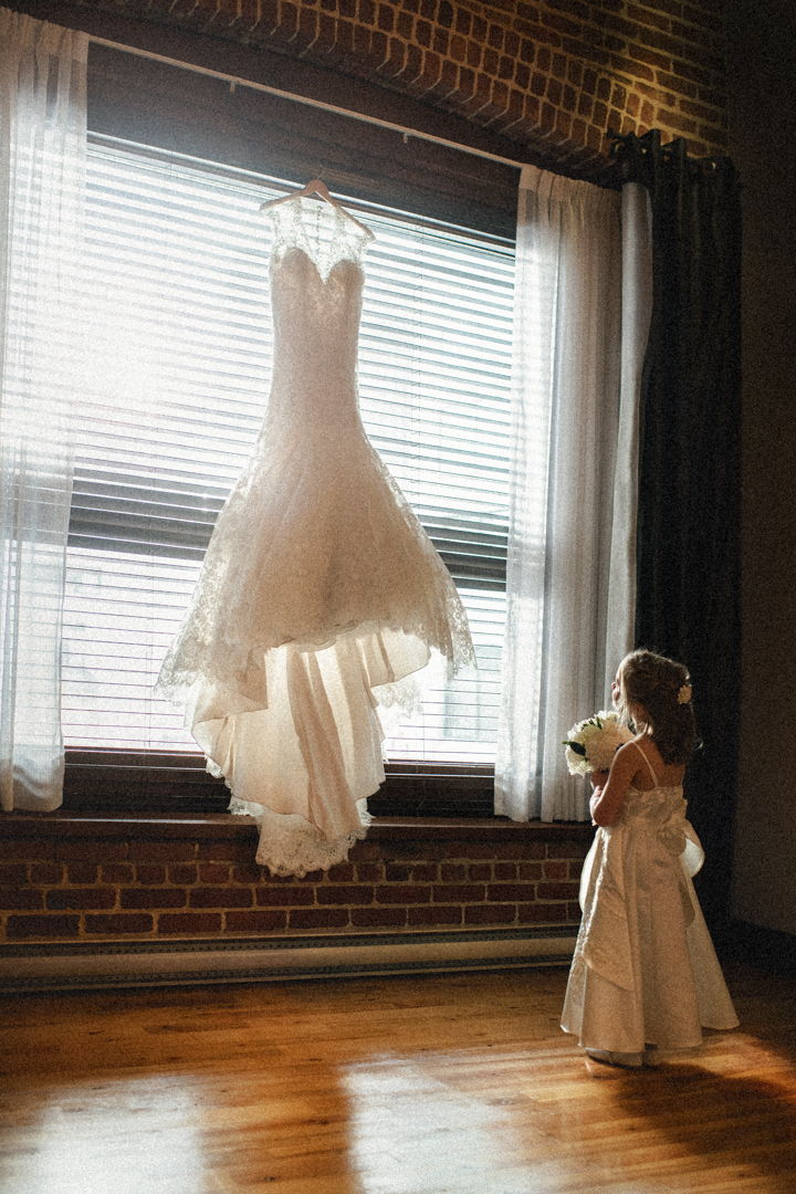 Small girl looking at a wedding dress hanging on the window