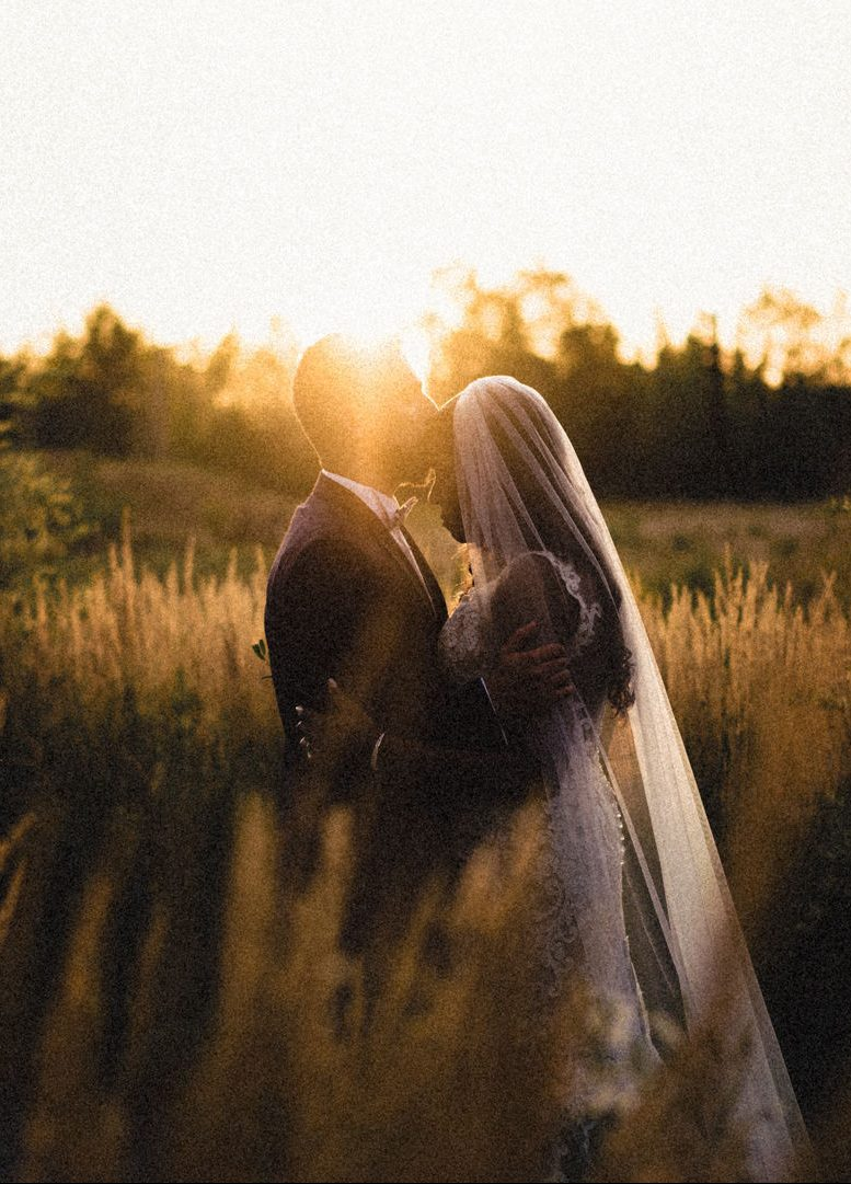 Romantic oicture of a couple in a field at their wedding day
