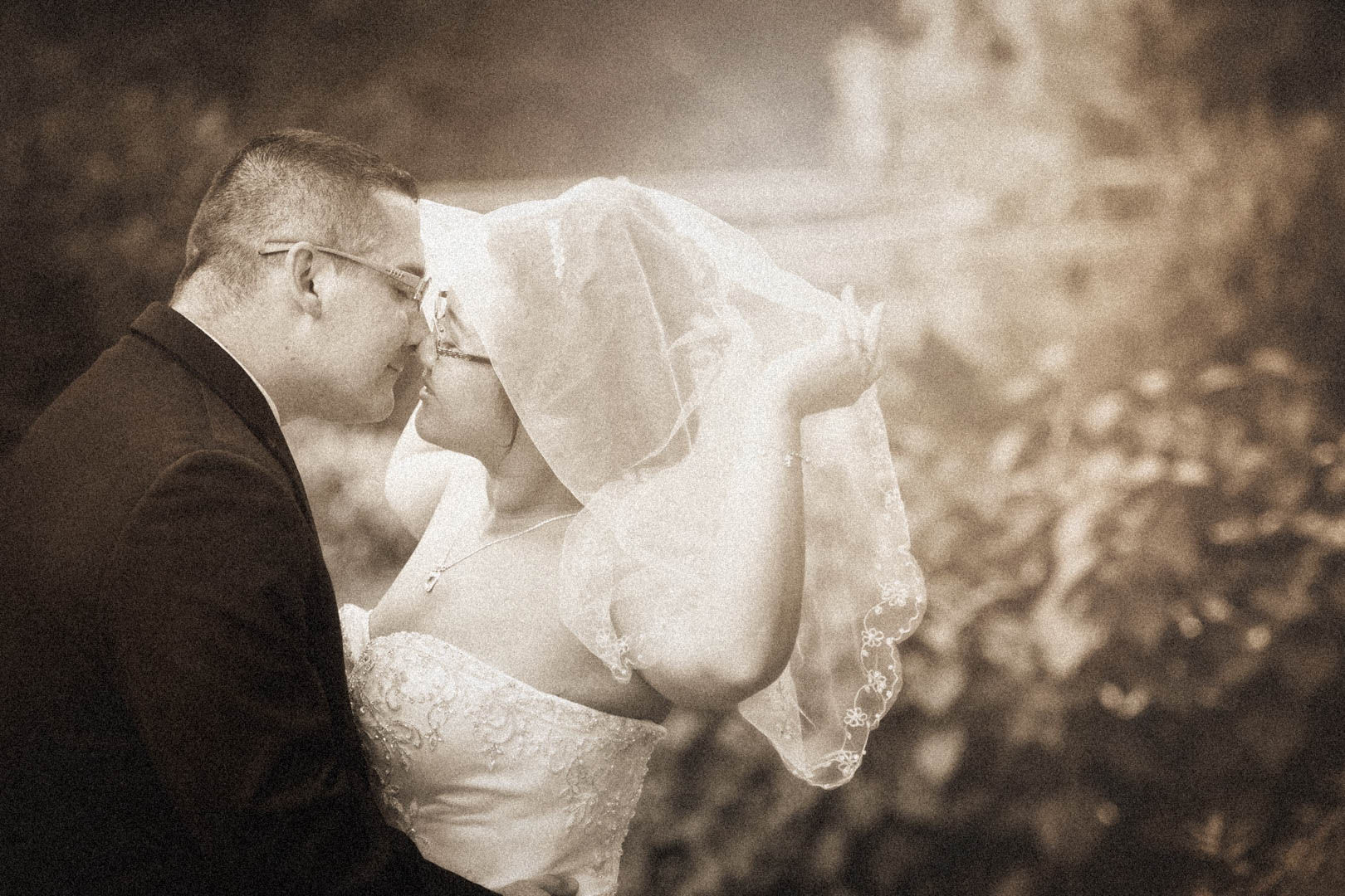 Bride kissing her groom while holding her veil