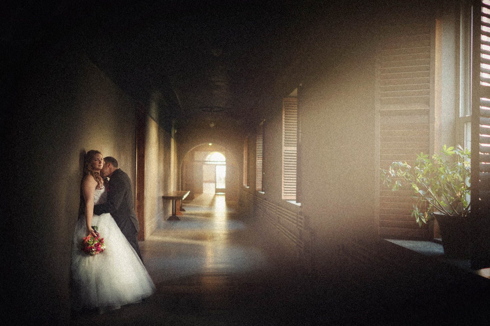 Bride and groom in a romantic hallway with sun rays on them